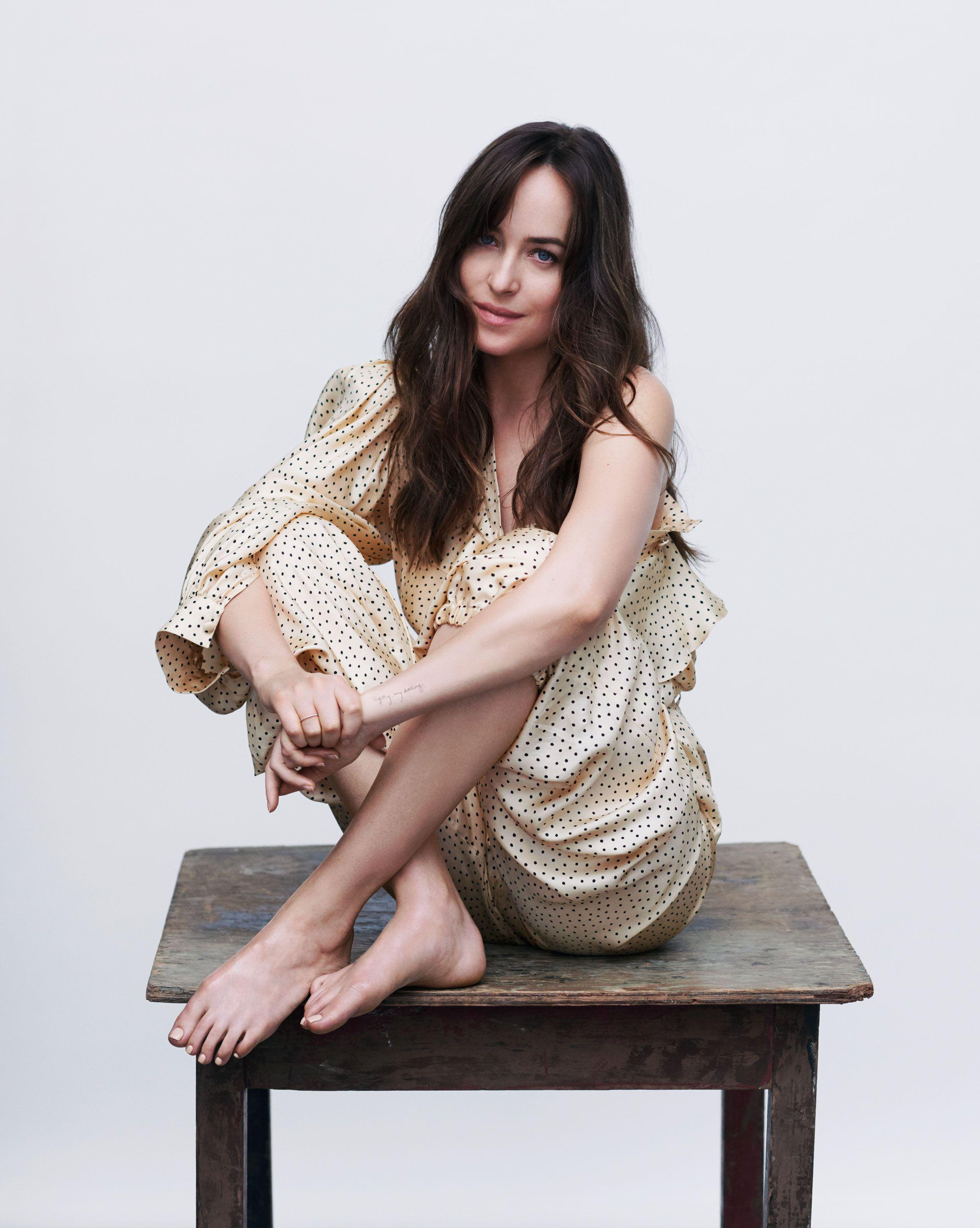 dakota Johnson sitting on a table - Dakota Johnson Net Worth, Movies, Family, Boyfriend, Pictures and Wallpapers